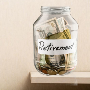 "A jar labeled ""Retirement"" is filled with money and sitting on a shelf."