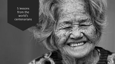 A black and white image of an elderly lady laughing.