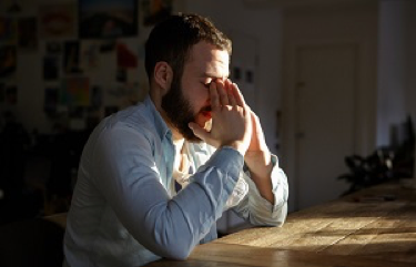 A man rests his head in his hands while sitting at a table.