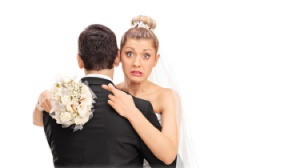 A nervous bride hugs her groom while crossing her fingers behind his back.