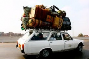 An old station wagon with a pile of luggage on top that amounts to a pile larger than the car itself.