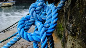 Divorce finance pictured as the untying of a knotted blue rope.