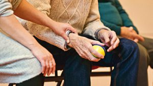 Later-life planning dpected by a young person embraces an elderly man who is using a ball for therapy.